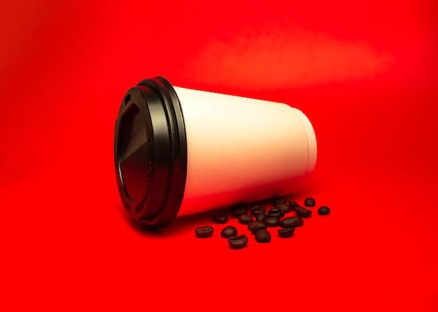 Papieren kopje koffie met bonen op een rode achtergrond.