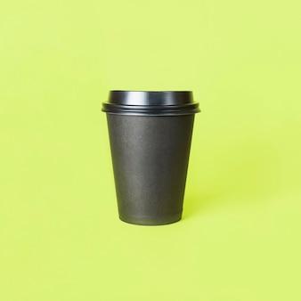 Papieren kopje koffie of thee op een groene achtergrond. bespotten. vooraanzicht mockup van lege polystyreen koffiemok. meenemen.