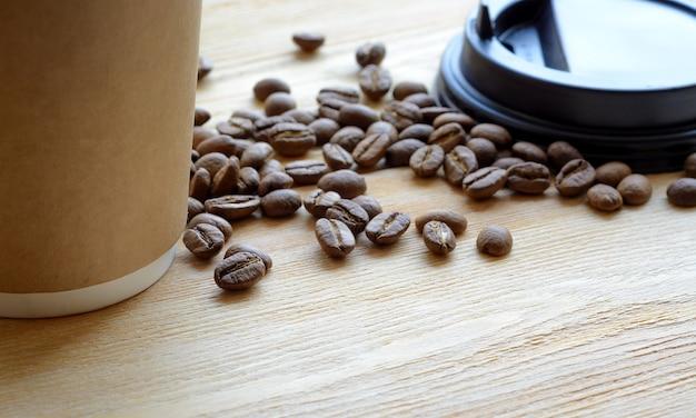 Papieren kopje koffie om mee te nemen en bonen op houten tafel. close-up met ondiepe dof.