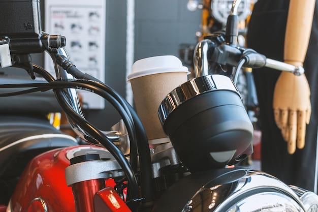Papieren kopje koffie op vintage motorfiets in moto lifestyle cafe en showroom