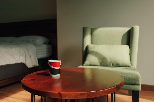 Papieren kopje warme drank op tafel met groene stoel in een klassieke gezellige bar.