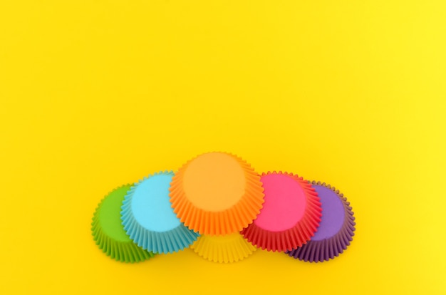 Papieren mallen voor het maken van cupcakes op gele achtergrond kleurrijke cupcakevormen