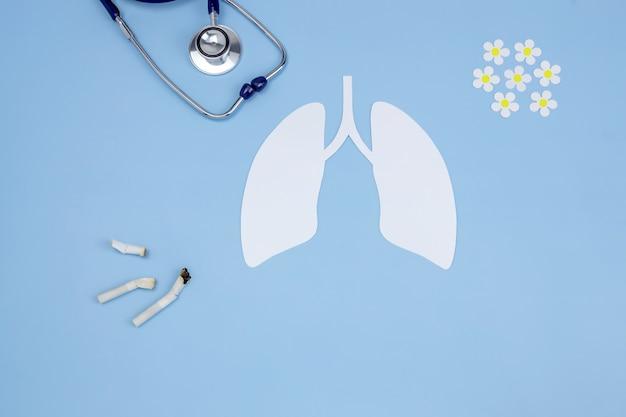 Papieren model van menselijke longen stethoscoop gerookte sigaretten en papieren madeliefjes
