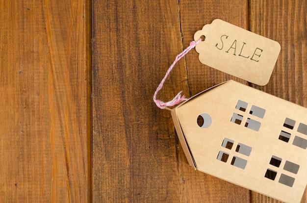 Papieren model van residentieel gebouw met verkooplabel