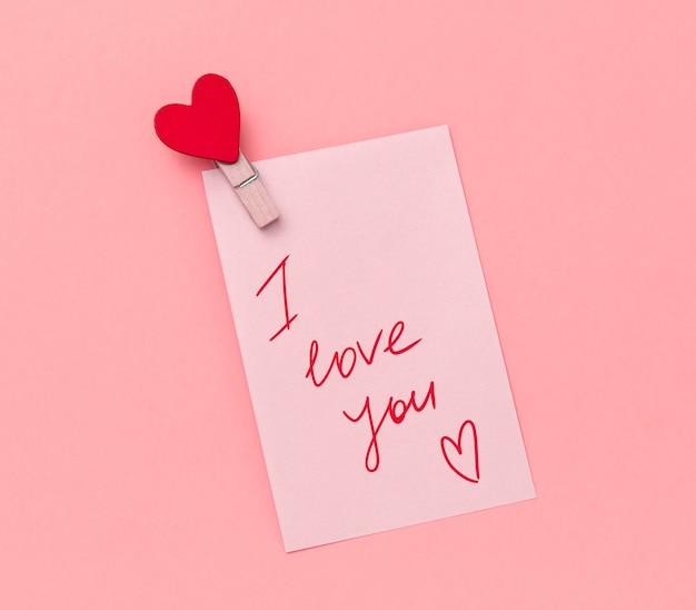 Papieren notitie met handgeschreven tekst ik hou van jou en stoffen pin versierd met rood hart