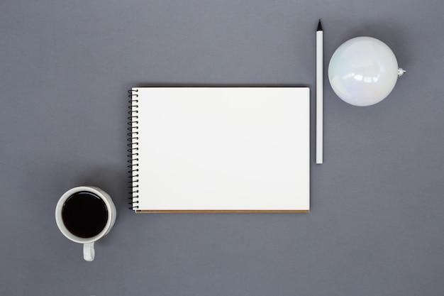 Papieren notitieblok, kopje koffie, potlood en kerstbal