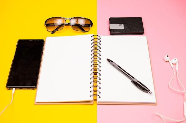 Papieren notitieboekje, smartphone, zonnebril en houder voor visitekaartjes op twee gekleurde achtergrond