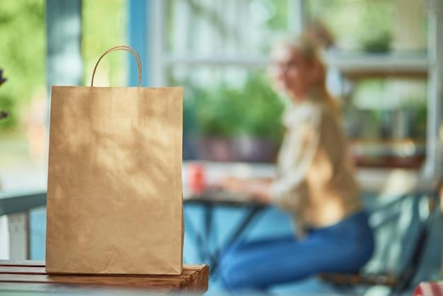 Papieren pakje op tafel op zakenvrouwenachtergrond