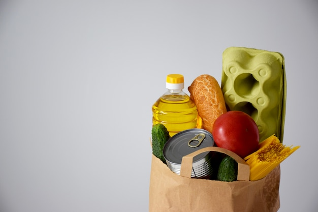 Papieren pakket met verschillende voedsel, olie, brood, eieren, tomaat, komkommer, blik, spaghetti