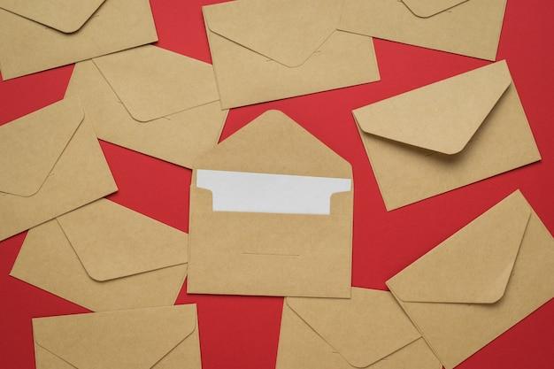 Papieren postenveloppen verspreid over een felrode achtergrond. het concept van postcorrespondentie. plat leggen.