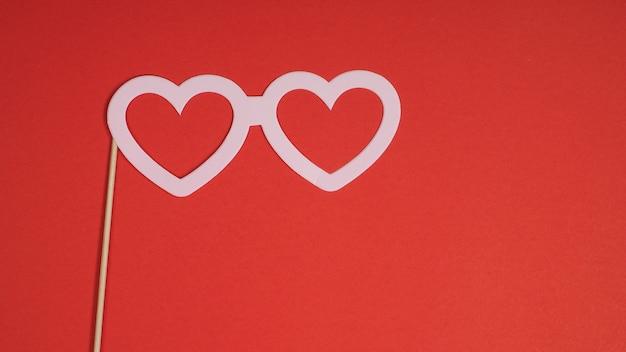 Papieren prop voor liefde of bruiloft teken op rode achtergrond.