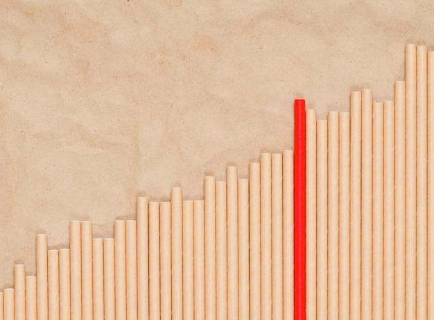 Papieren rietjes voor drankjes zijn neergelegd in de vorm van een oplopende curve van een grafiek op ambachtelijk papier, een van de rietjes is rood