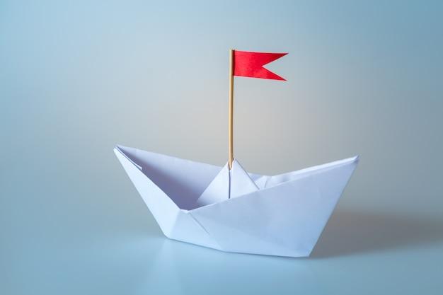 Papieren schip met rode vlag op blauw