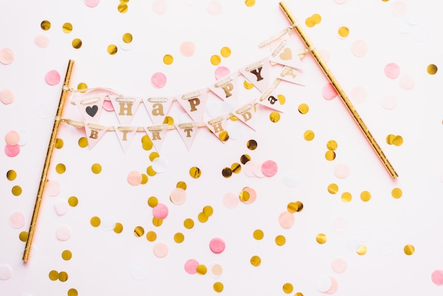 Papieren slinger streamer met gefeliciteerd. fijne verjaardag. roze gelukkige verjaardag achtergrond en confetti. sjabloon voor felicitaties, blog, kortingen en reclame