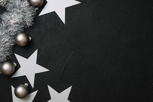 Papieren sterren met kerstballen op tafel