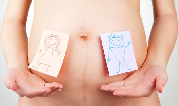 Papieren stickers op de buik van een zwangere vrouw