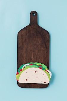 Papieren taco op houten bord bovenaanzicht
