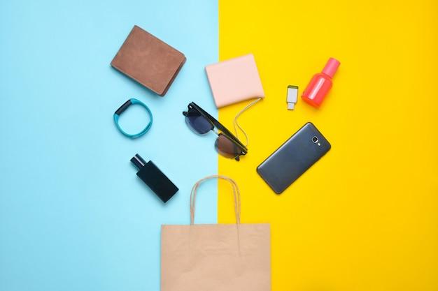 Papieren tassen en veel aankopen van gadgets en accessoires op een gekleurde achtergrond: zonnebril, smartphone, slimme armband, powel bank, usb stick, portemonnee. consumentenconcept. bovenaanzicht