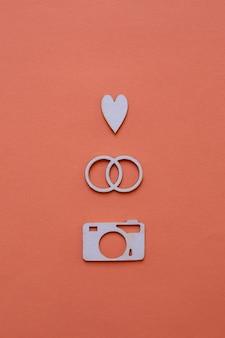 Papieren trouwringen, hart en camera