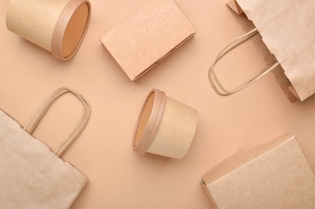 Papieren verpakking op een beige ondergrond. eten bezorgen, afhaalmaaltijden. milieubescherming. zero waste. platte lay-out, bovenaanzicht, een plek om te kopiëren.