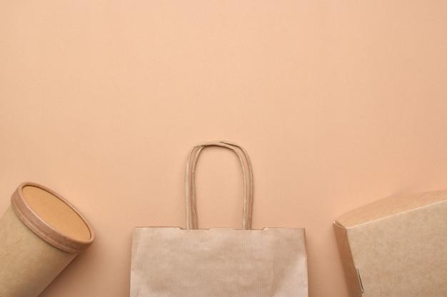 Papieren verpakking op een beige ondergrond. eten bezorgen, afhaalmaaltijden. milieubescherming. zero waste.