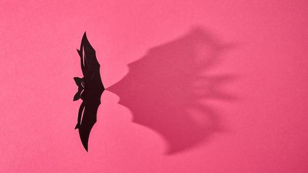 Papieren vliegende handgemaakte vleermuis gepresenteerd op een rode achtergrond met een patroon van schaduwen en ruimte voor tekst. halloween. plat leggen