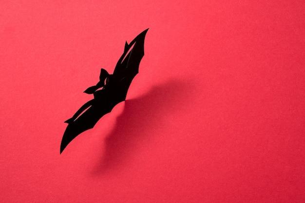 Papieren vliegende handwerkvleermuis gepresenteerd op een rode achtergrond met een patroon van schaduwen en ruimte voor tekst. mystieke halloween-lay-out. plat leggen