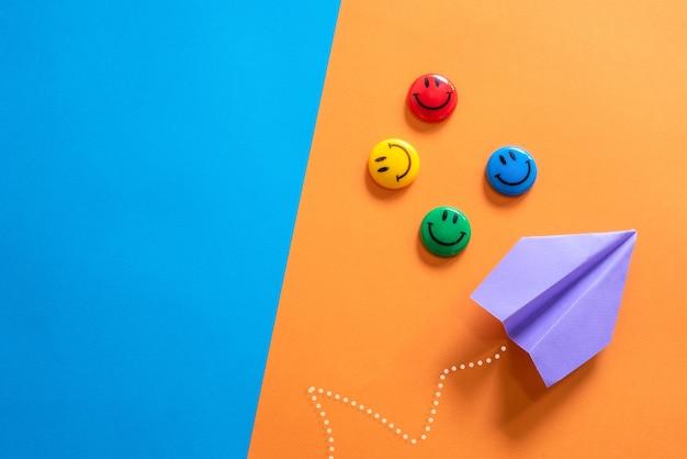 Papieren vliegtuig en smileygezicht op blauwe en oranje achtergrond verschillende visie creatief en innovatief