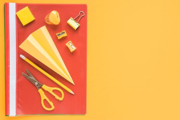 Papieren vliegtuig omringd door oranje kantoorbehoeftenvoorwerpen