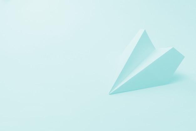 Papieren vliegtuig op een lichtblauwe achtergrond.