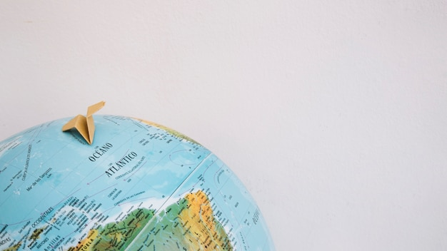 Papieren vliegtuig op wereldbol