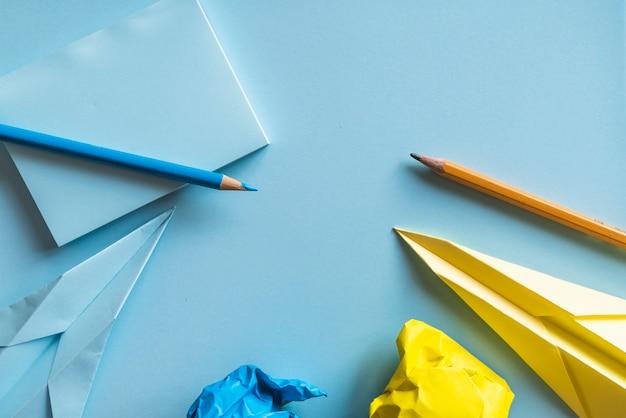 Papieren vliegtuigen en potloden