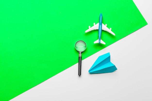 Papieren vliegtuigen op pastel gekleurde achtergrond. jeugd, vrijheid en diversiteit concept