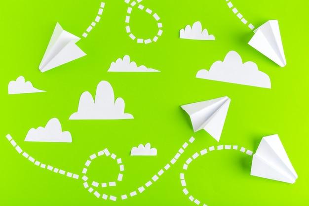 Papieren vliegtuigen verbonden met stippellijnen op groen oppervlak.