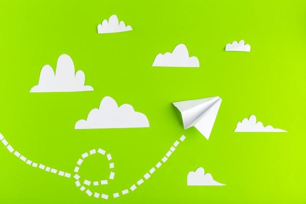 Papieren vliegtuigen verbonden met stippellijnen op groene achtergrond. bedrijf