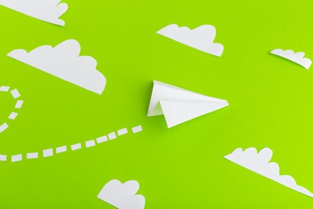 Papieren vliegtuigen verbonden met stippellijnen op groene achtergrond. bedrijfsconcept