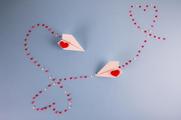 Papieren vliegtuigen vliegen met hart snoepjes