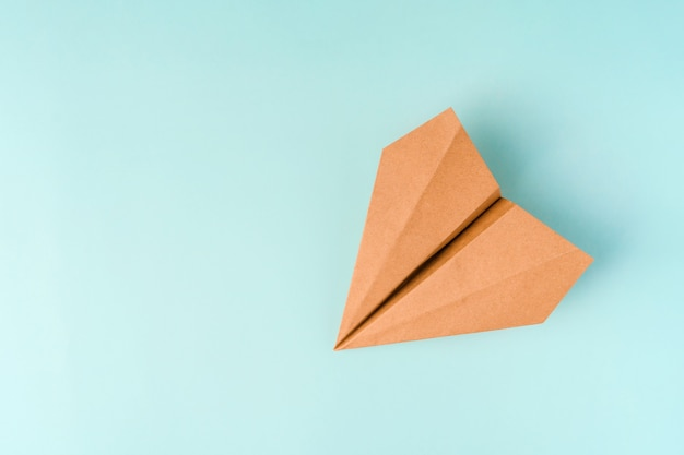 Papieren vliegtuigje gemaakt van kraftpapier op een lichtblauwe achtergrond, ruimte voor tekst