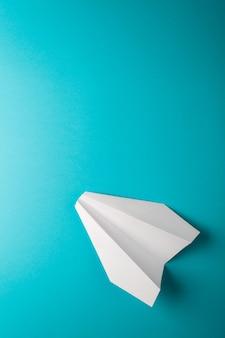 Papieren vliegtuigje op blauwe ondergrond