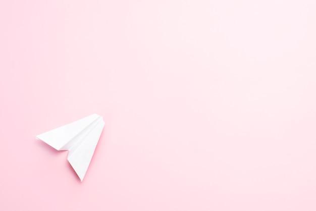 Papieren vliegtuigje op een roze achtergrond.
