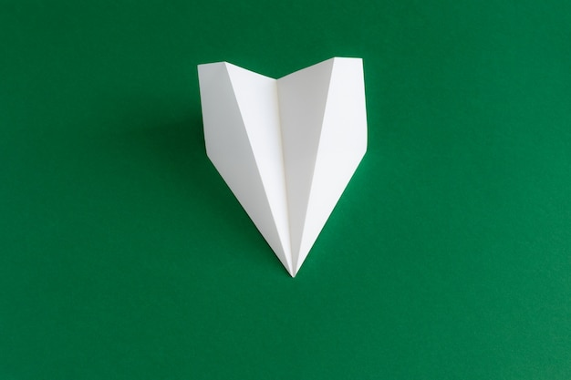 Papieren vliegtuigje op groen
