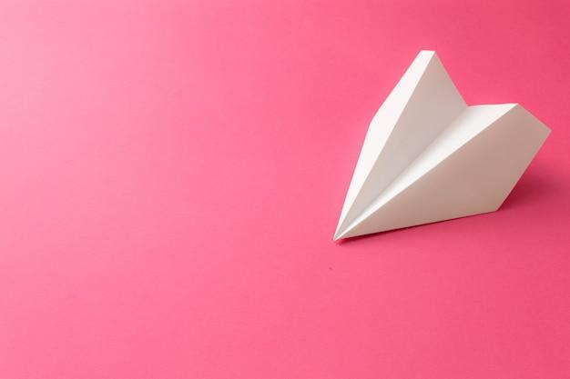 Papieren vliegtuigje op roze