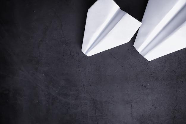 Papieren vliegtuigje op tafel. origamimodel op een donkere achtergrond. concept. creatieve verspilling van tijd.