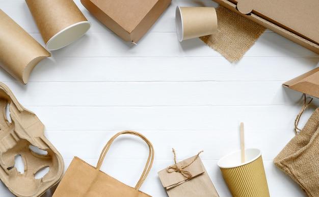 Papieren voedselverpakkingen van milieuvriendelijke materialen op witte tafel