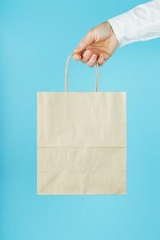 Papieren zak at arm's, bruine ambachtelijke tas voor afhaalmaaltijden geïsoleerd op blauwe achtergrond sjabloonlay-out van de verpakking met ruimte voor kopiëren, reclame.