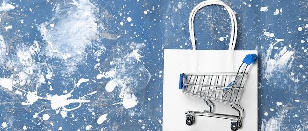 Papieren zak, boodschappentas en trolley op blauw.