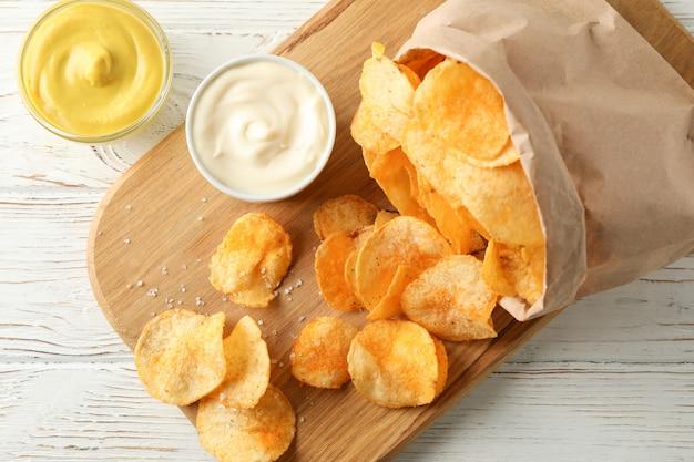 Papieren zak chips. biersnacks, saus op scherpe raad, op witte houten, ruimte voor tekst. bovenaanzicht