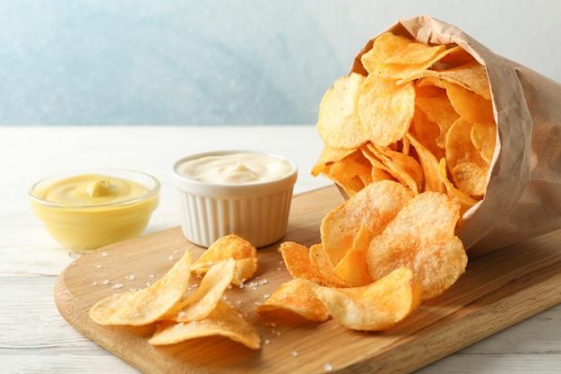 Papieren zak chips. biersnacks, saus op scherpe raad, op witte houten, ruimte voor tekst. detailopname