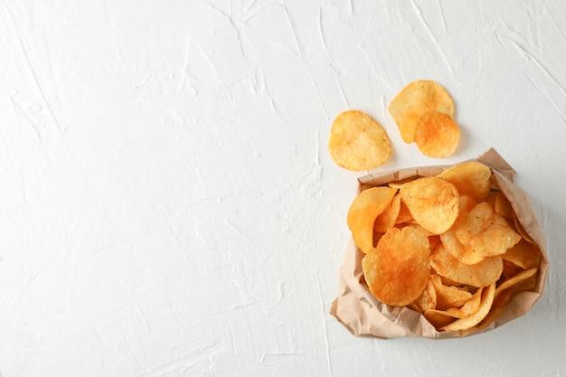 Papieren zak chips op witte houten, ruimte voor tekst. bovenaanzicht