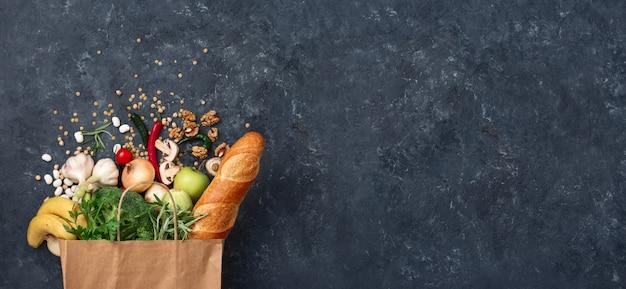 Papieren zak groenten en fruit op een donkere met kopie ruimte bovenaanzicht. zak voedsel concept